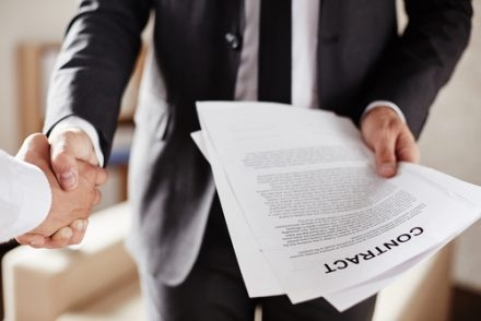 two businessmen shaking hands with a contract