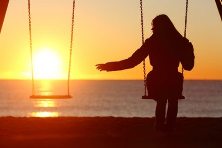 woman sitting alone on a swing at sunset