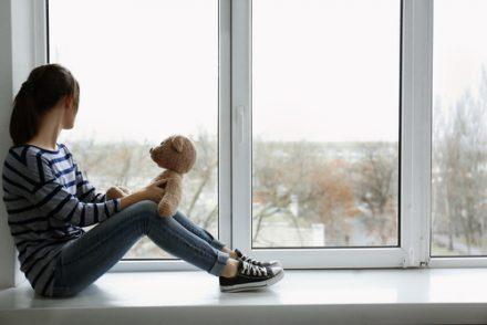 sad girl on a windowsill with her teddy