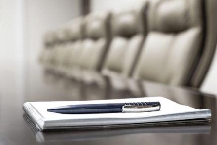 boardroom table with pen and paper