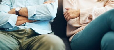 Mature couple sitting on the sofa with their arms folded after an argument