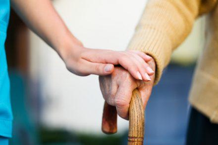 nurse holding elderly hand