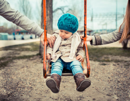 girl on swing being tugged by both parents, separation concept