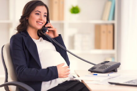 Happy Pregnant Woman Talking On The Phone while working